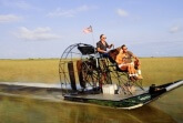USA, Florida, Everglades National Park, people riding airboat over wet